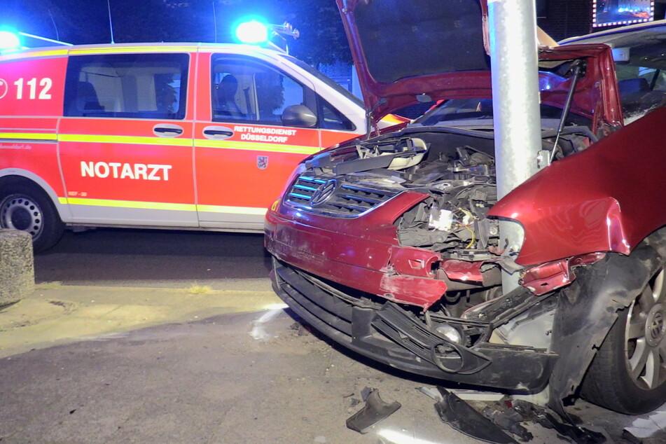 Der Unfallwagen ist mit der Motorhaube an einer Straßenlaterne stecken geblieben.