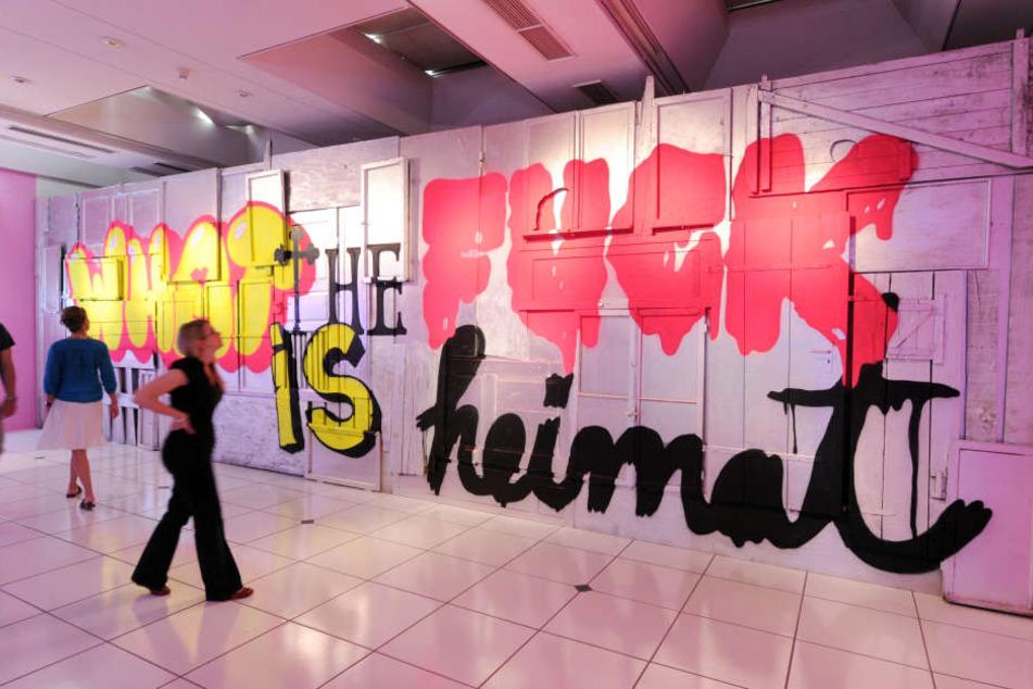 """Besucher des Museum beim Markt betrachten das Werk """"What the fuck is heimat?"""" aus dem Jahr 2012 von dem Künstler Stefan Strumbel."""