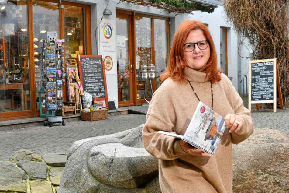 """Feng-Shui-Expertin Annett Hering (51) blättert vor ihrem Laden in der Kunsthof-Passage in ihrem """"Rauhnächte""""-Work-Book."""