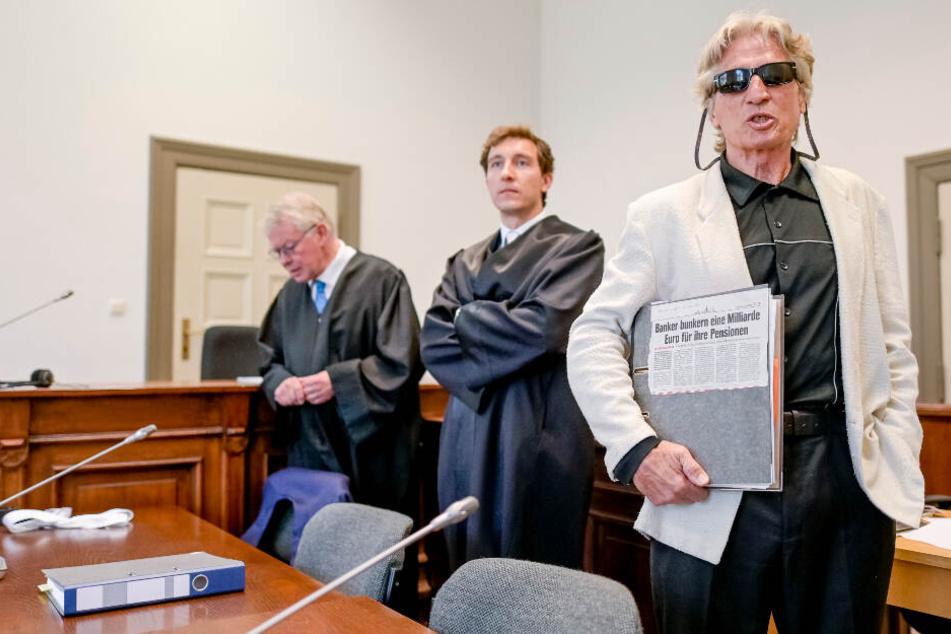 Der 70-jährige mutmaßliche Serienbankräuber (rechts), wartet neben seinen Anwälten auf den Beginn der Verhandlung.