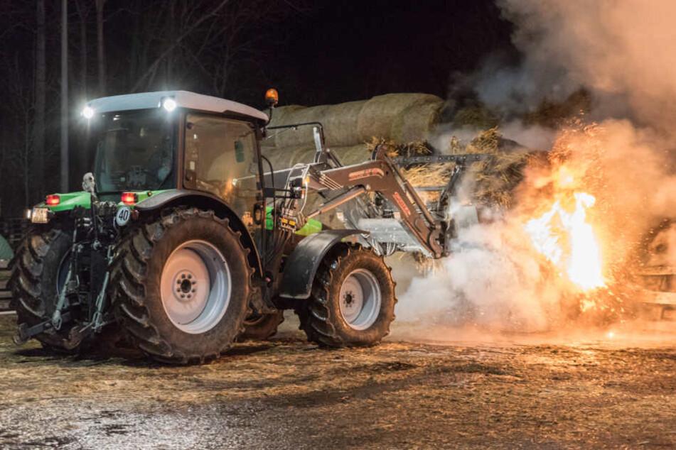Mit Hilfe des Traktors wurden die brennenden Strohballen auseinandergezogen und schließlich abgelöscht.