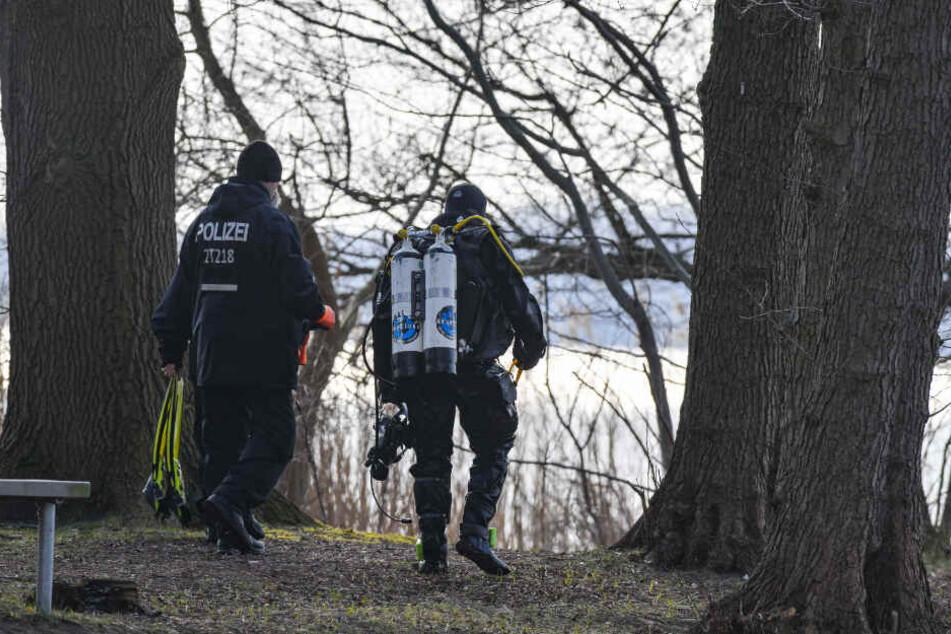 Ein Polizeitaucher geht am Ufer des Wolziger Sees im Landkreis Dahme-Spreewald entlang.