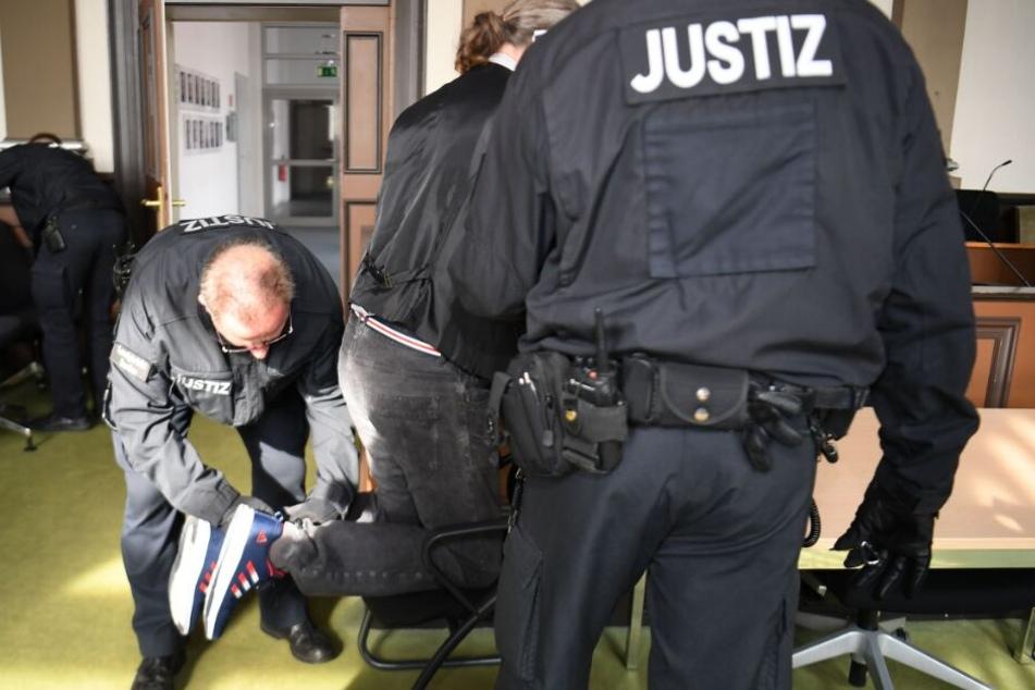 Justizbeamten nehmen dem Angeklagten die Fußfesseln ab.