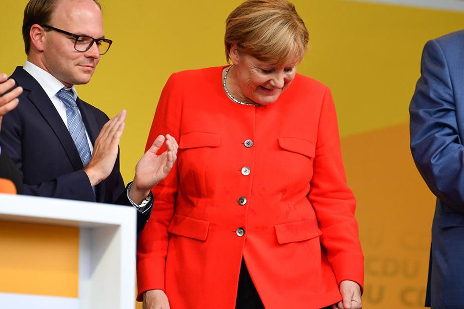 Angela Merkel schaut auf ihren Tomatenfleck und muss lachen.