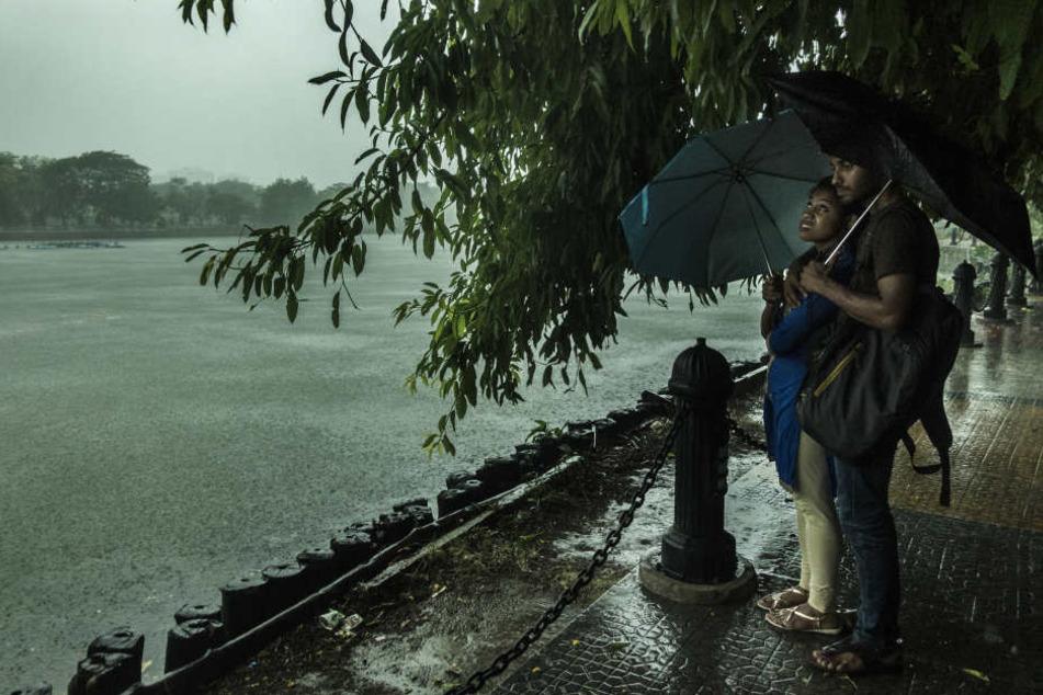 In Kalkutta suchen Menschen Schutz vor dem Regen während starker Regenfälle und Stürme.