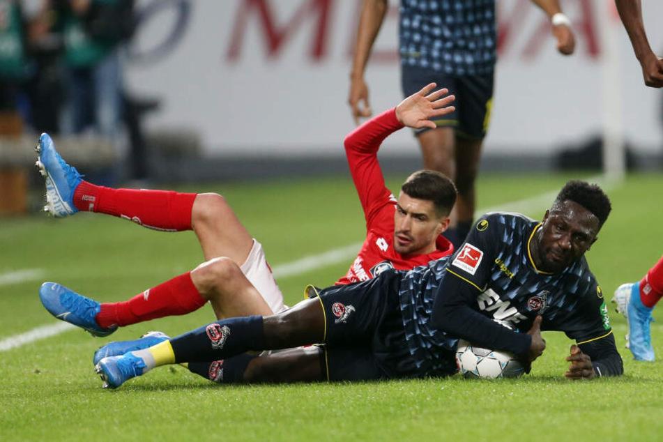 Der Kölner Kingsley Schindler (r) und der Mainzer Aaron Martin kämpfen um den Ball.