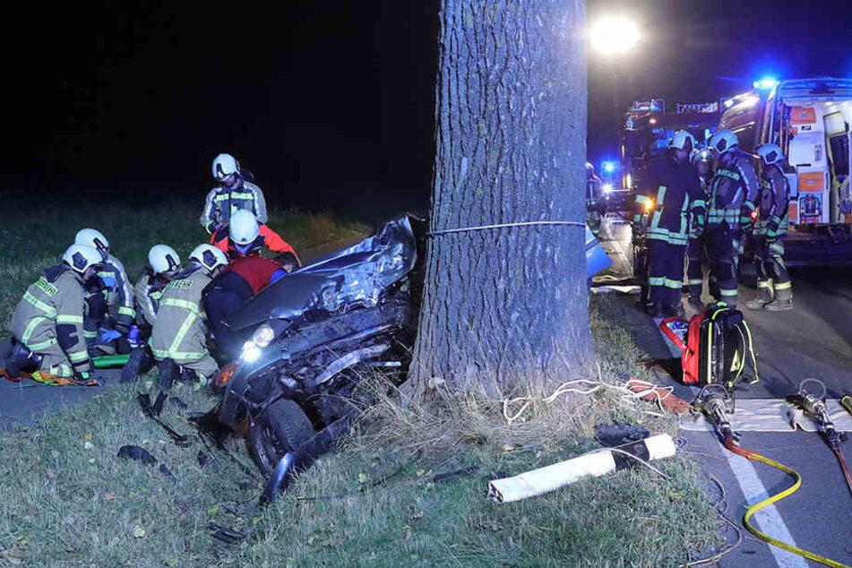 Retter kümmern sich um dem Mann, der nach dem schweren Unfall in seinem Auto eingeklemmt ist.