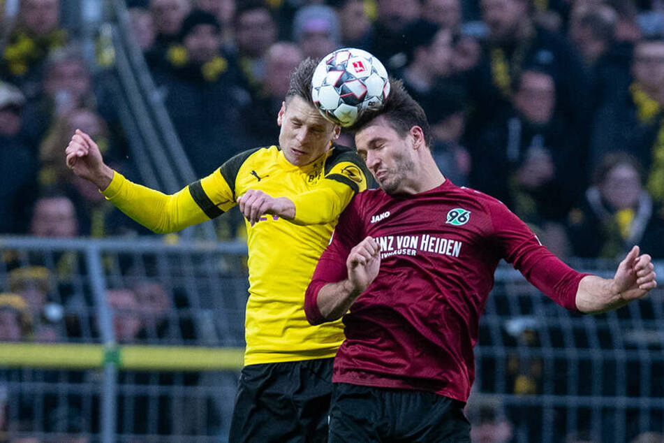 Zwei auffällige Kicker im Kopfballduell: Dortmunds Lukasz Piszczek (l.) und Hannovers Sturmtank Hendrik Weydandt (r.).