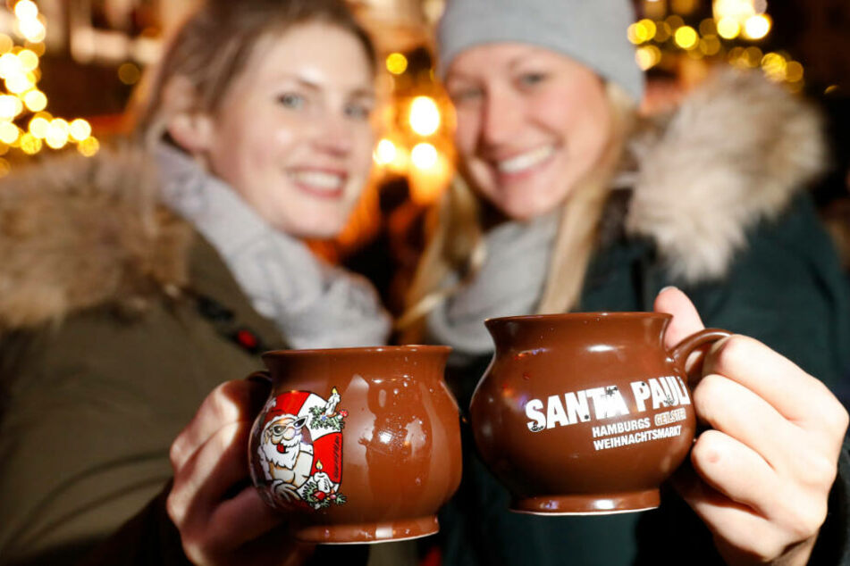 Dazu ist Glühwein da: Zwei Frauen stoßen mit dem Heißgetränk auf einem Hamburger Weihnachtsmarkt an. (Archivbild)