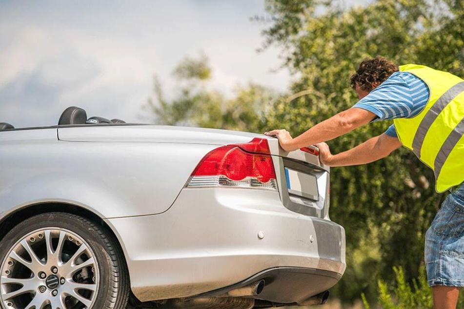 Nach dem Sprit ging dem schiebenden Autofahrer auch noch die Puste aus, doch sein Beifahrer eilte mit einem Kanister zu Hilfe. (Symbolbild)
