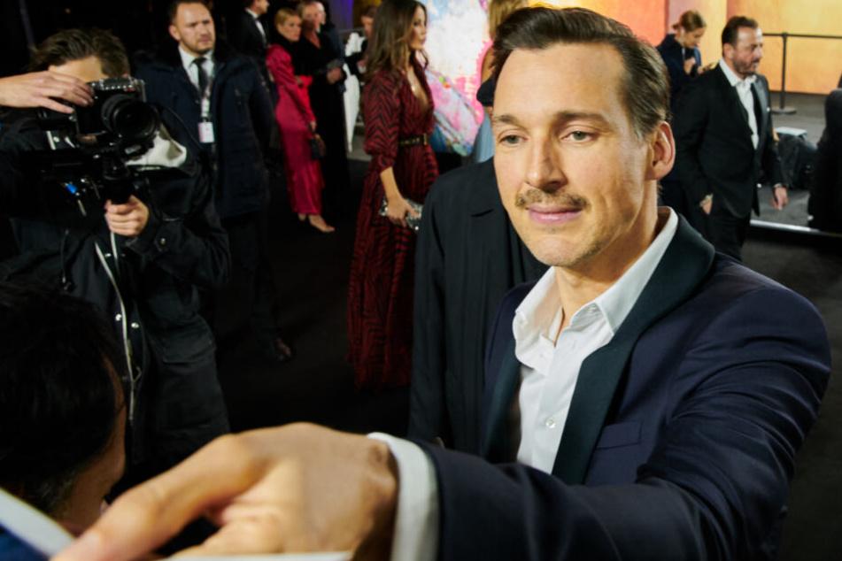 """Florian David Fitz (44), Schauspieler, gibt Autogramme vor der Gala """"Men of the Year"""" des Magazins GQ in Berlin."""