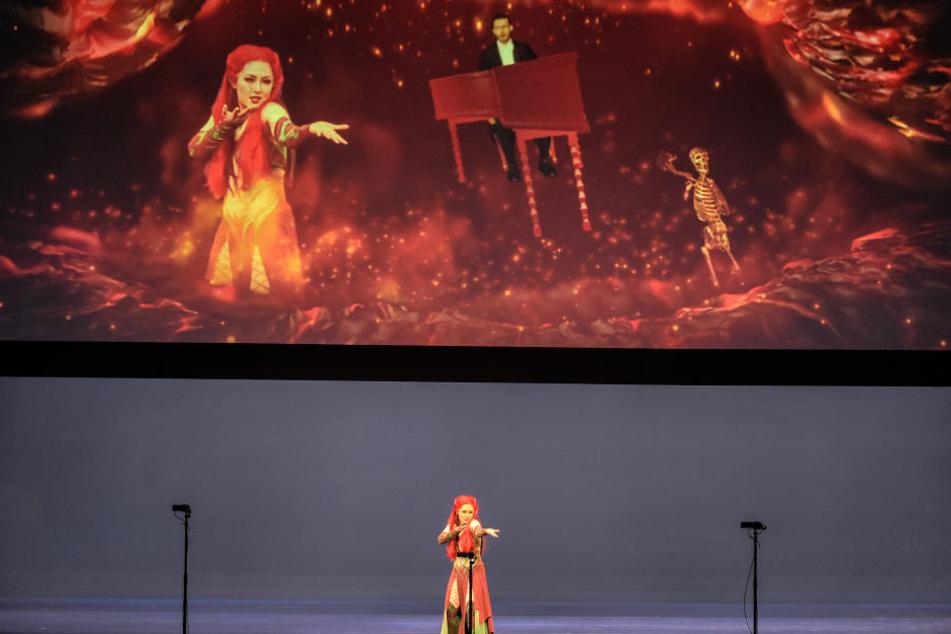 Während auf der fast leeren Bühne gesungen wird, montiert die moderne Technik  die Sängerin in ein Szenenbild.