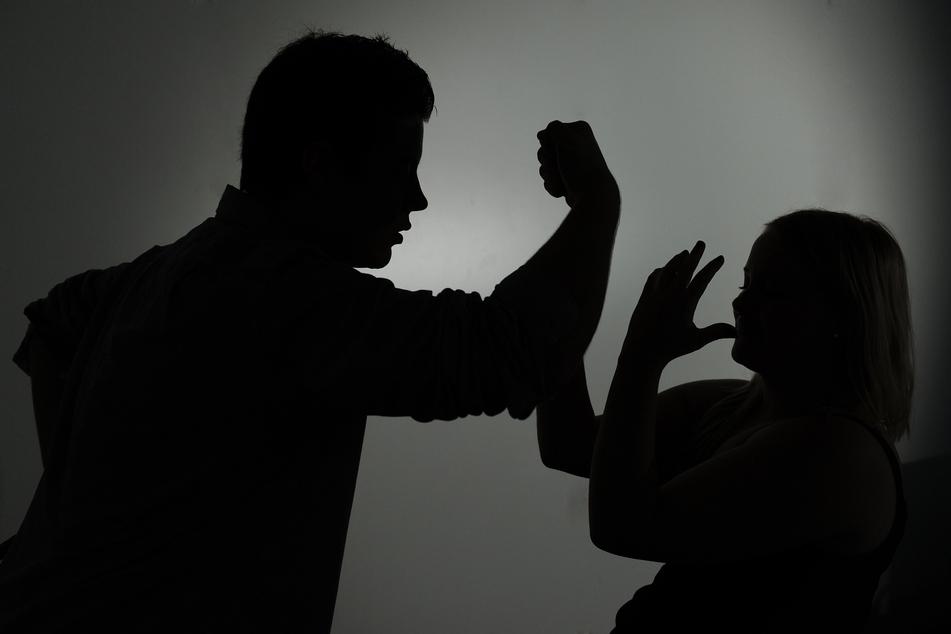 Ein Mann droht einer Frau mit der Faust (Illustration).