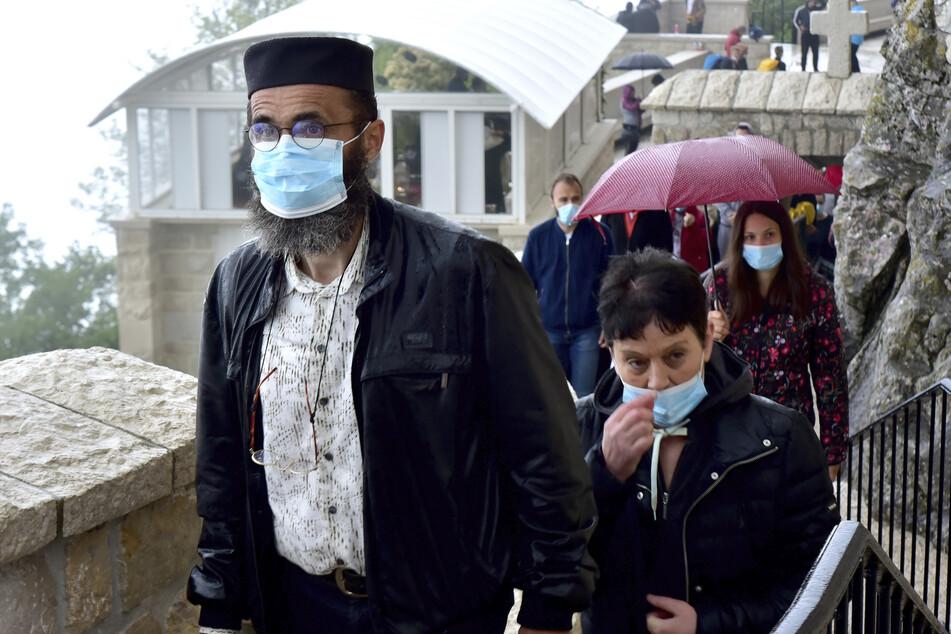 Gläubige mit Mundschutzen warten in einer Schlange vor dem christlich-orthodoxen Kloster von Ostrog.