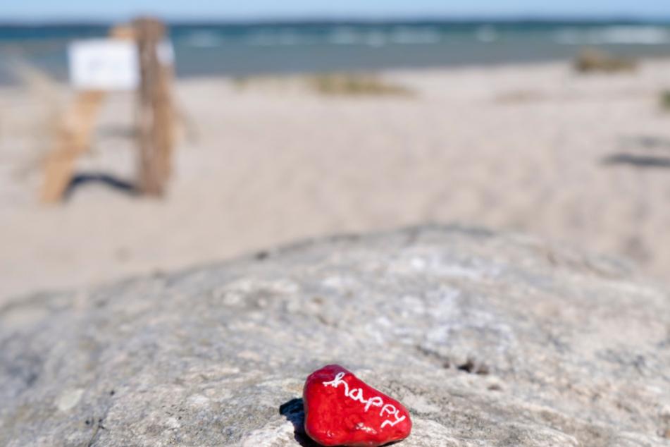 Auf dem Stein steht happy. Das dürfte in den nächsten Wochen aber niemand sein, der Urlaub machen will...