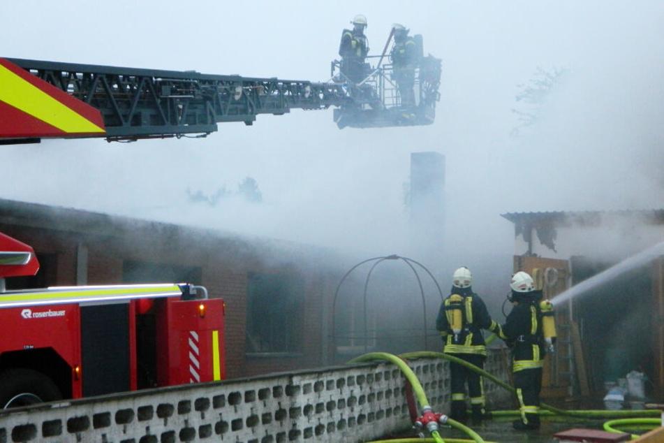 Feuerwehrleute löschen von einer Drehleiter aus den Brand.
