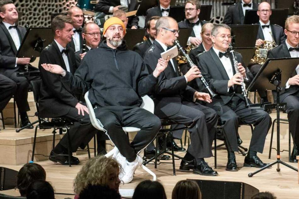 Der Rapper liest in der Elbphilharmonie während eines Konzerts vor.
