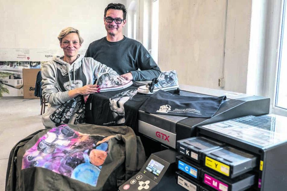 """Gründer Hendrik Rottluff (48) und Künstlerin Denise Kendzia (38) mit der Textildruckmaschine in """"Karl's Kunsthaus""""."""