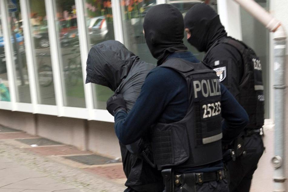 Ein Verdächtiger wird von SEK-Polizisten abgeführt.