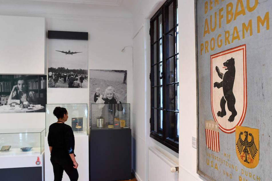 Eine Besucherin schaut sich eine Dokumentation aus der Zeit der Luftbrücke an.