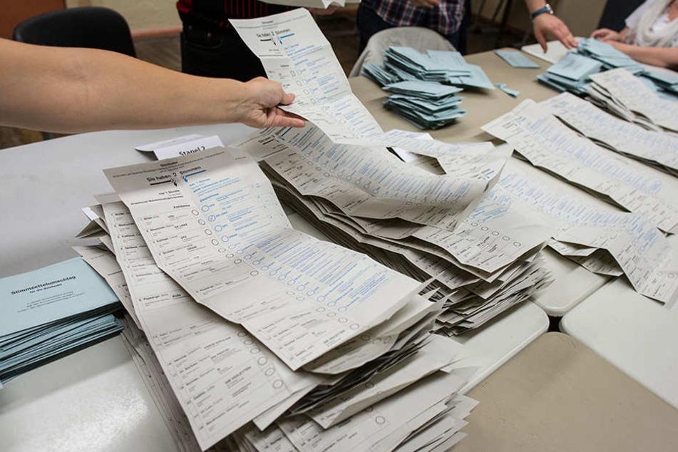 Wahlhelfer sortieren Stimmzettel zur Bundestagswahl in einem Wahllokal in Friedrichshain.