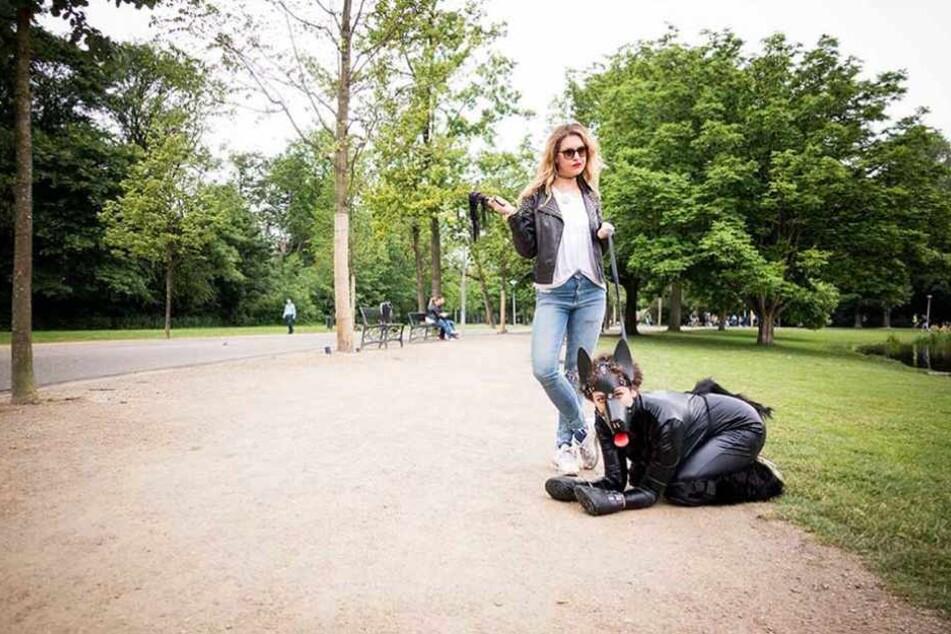 Ines führt Leila im Fetish-Hundekostüm durch den Park.