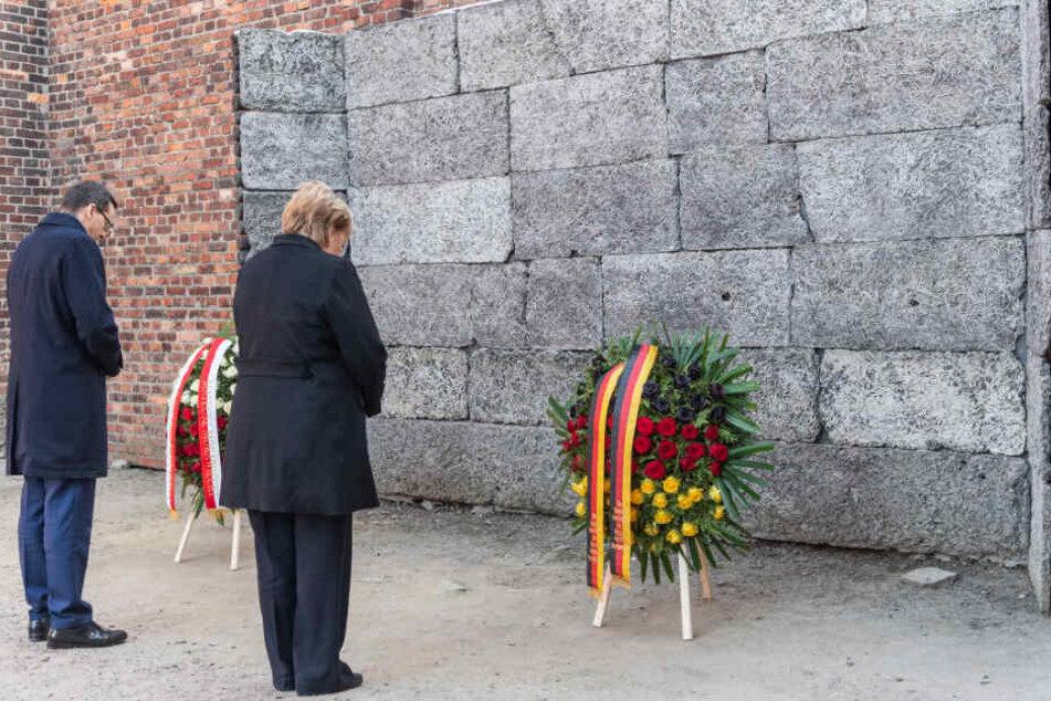 Bundeskanzlerin Angela Merkel (CDU) und Mateusz Morawiecki, Ministerpräsident von Polen, stehen bei einer Kranzniederlegung an der Todesmauer im ehemaligen deutschen Konzentrationslager Auschwitz.