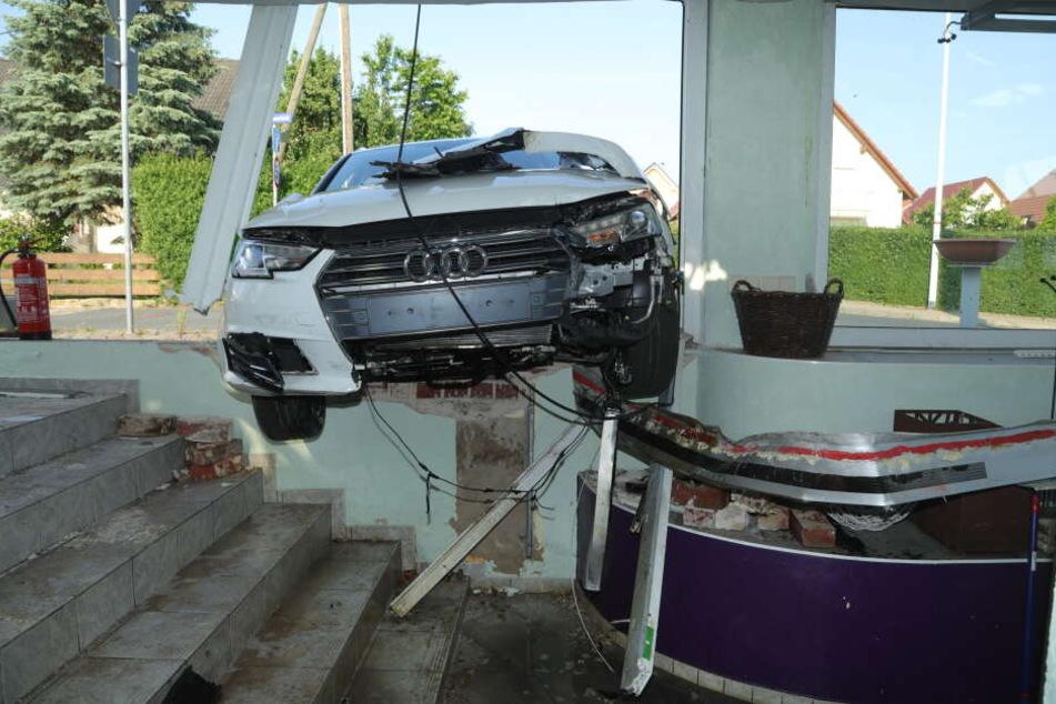 Der Audi blieb auf einer Betonkante hängen.