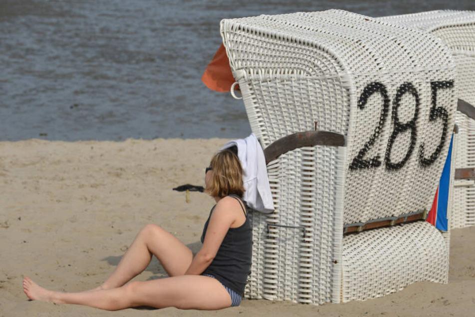 Eine junge Frau sonnt sich an einem Strandkorb an der Nordsee. (Archivbild)
