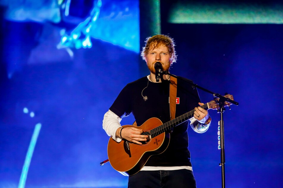 Ed Sheeran performs on a stage.