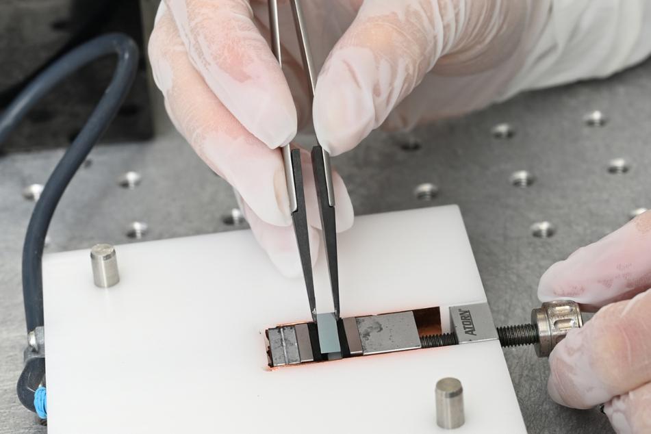 Stuttgart: In einem Labor der Firma Q.ANT wird von einer Ingenieurin ein neu entwickelter Chip zum Einsatz in einen Quantencomputer in eine Kontrollvorrichtung eingelegt.