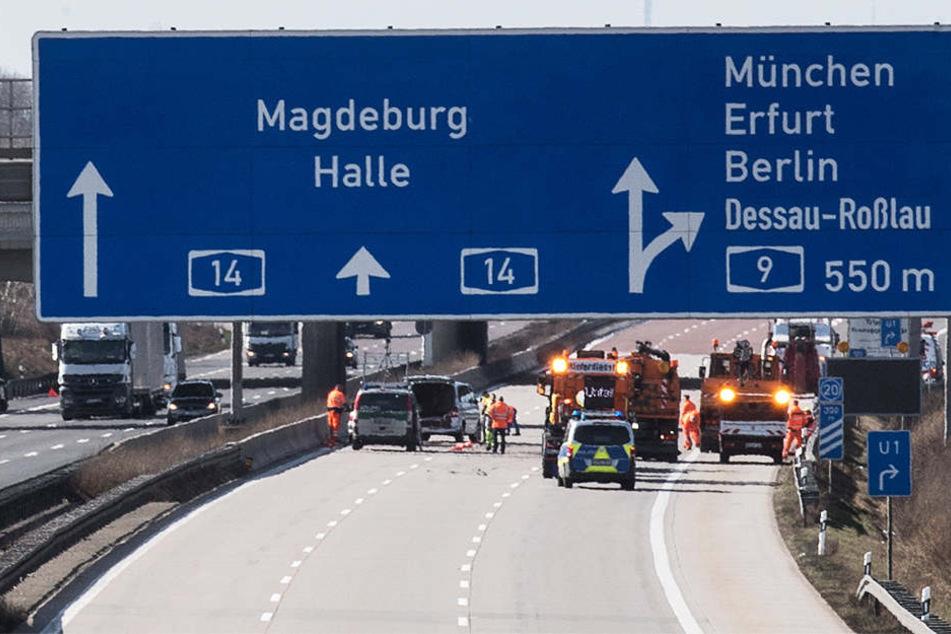 Voll gesperrt: Einsatzkräfte beseitigen die Trümmerteile, die sich bei dem Unfall auf der kompletten Fahrbahn verteilt hatten.