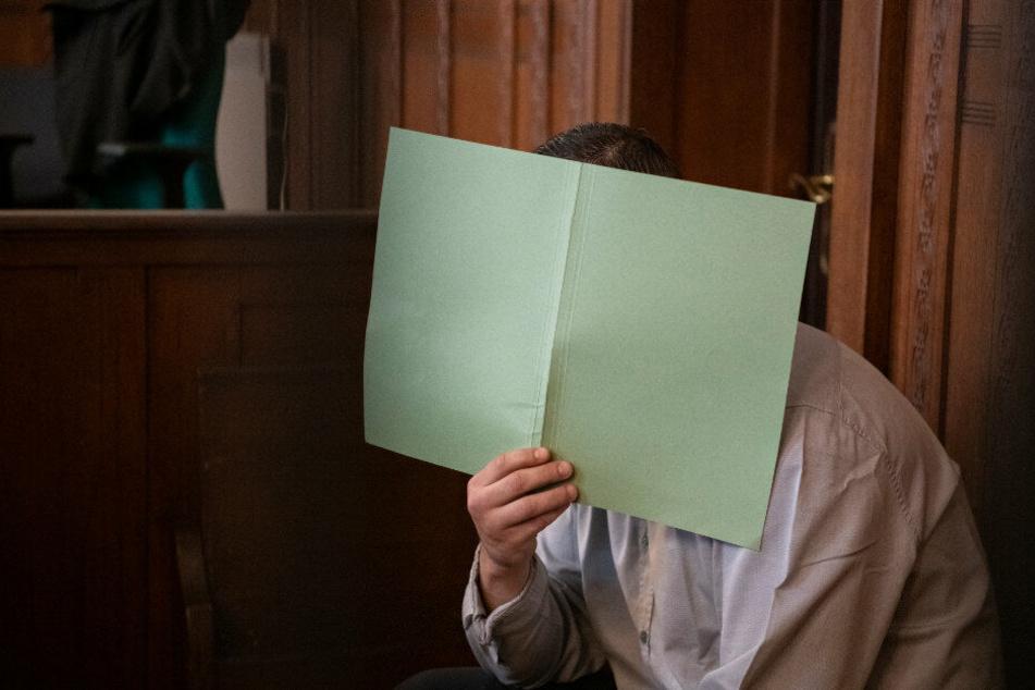 Der Angeklagte hält sich in einem Gerichtssaal im Landgericht ein Papier vor sein Gesicht.
