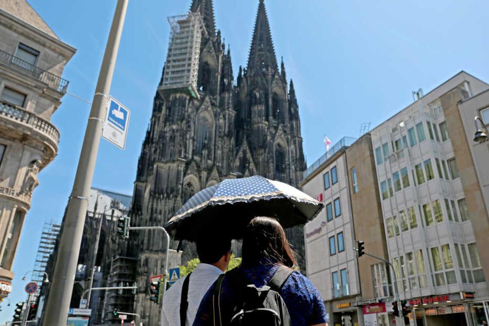 In Köln laufen die Touristen bereits mit Sonnenschirmen durch die Altstadt und schauen sich die Sehenswürdigkeiten wie den Kölner Dom an.