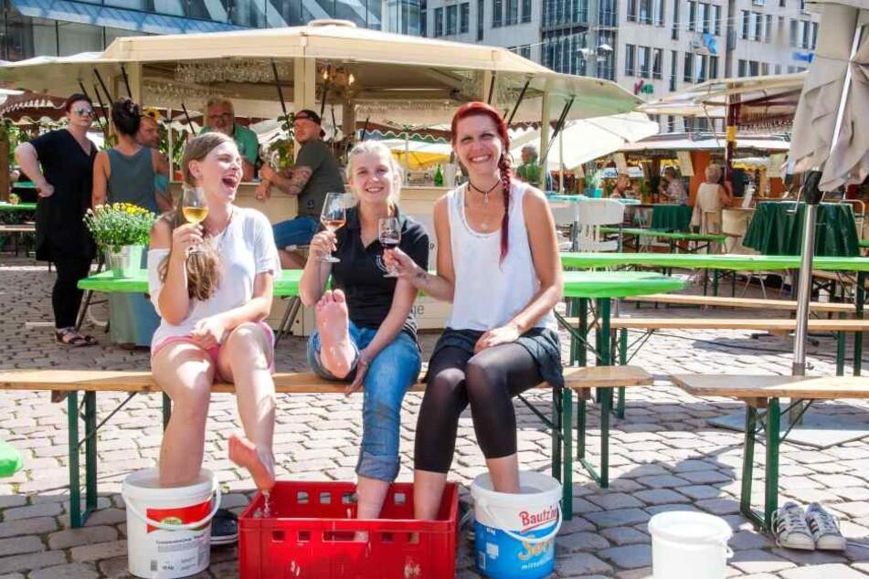 Kara Alvina Enzian (16), Annekatrin Rades (28) und Nancy Enzian (34) kühlen sich auf dem Weindorf mit kaltem Wasser ab.