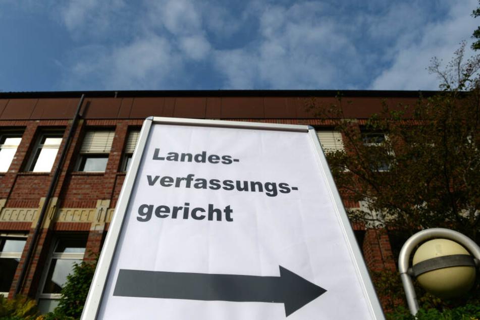 """Ein Schild mit der Aufschrift """"Landesverfassungsgericht"""" weist den Weg zum Sitzungssaal des Landesverfassungsgerichts in Schleswig-Holstein."""