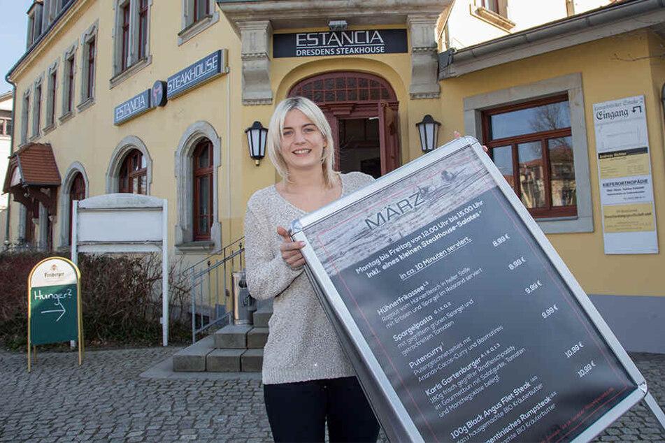 """Chefin Alisa Zuber (27) platziert den Aufsteller für das März-Mittagsangebot vor ihrem neuen """"Estancia""""-Steakhaus in Klotzsche."""