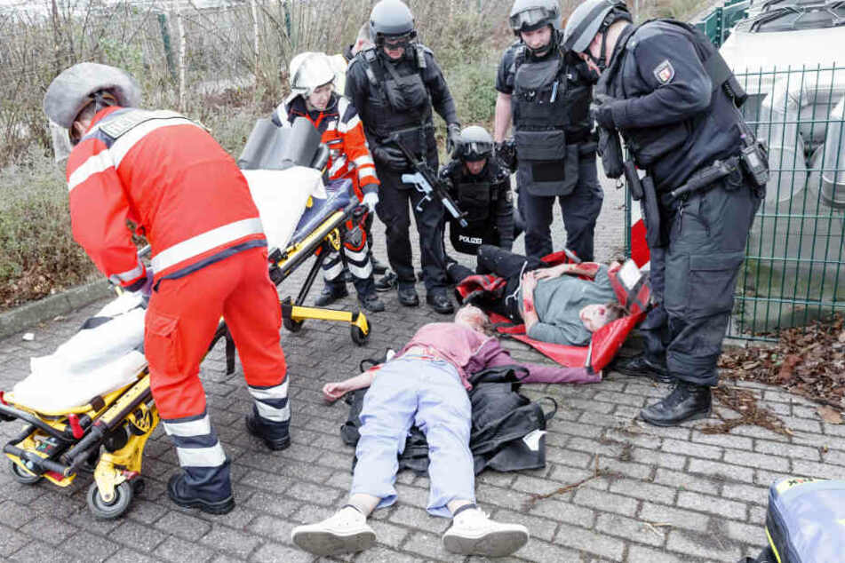 Rettungsdienst und Polizisten versorgen Verletzte, die von freiwilligen Helfern gespielt werden.
