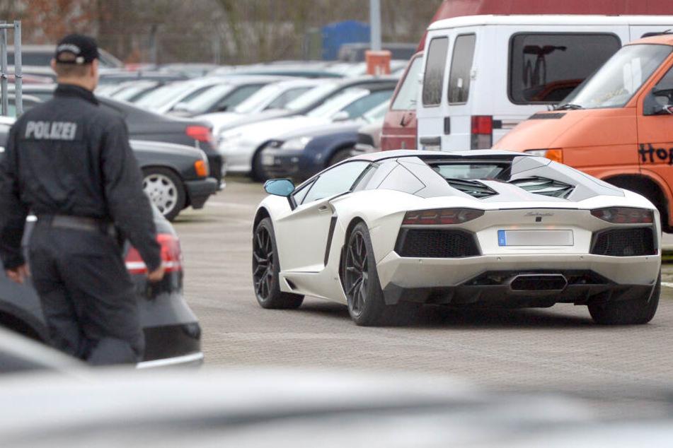 Ein Polizeibeamter blickt auf einen fahrenden Lamborghini. (Symbolbild)