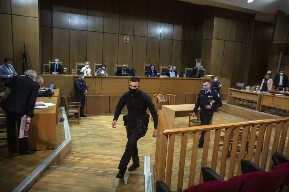 """Polizeibeamte gehen mit Mund-Nasen-Schutz beim Prozess gegen die rechtsextreme griechische Partei (Golden Dawn) """"Goldene Morgenröte"""" durch den Gerichtssaal."""