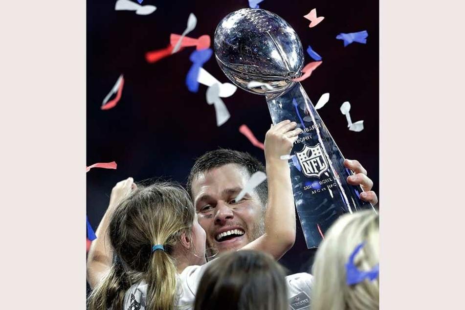Tom Brady von den Patriots hält nach dem gewonnenen Spiel seine Tocher und die Vince Lombardi Trophäe.