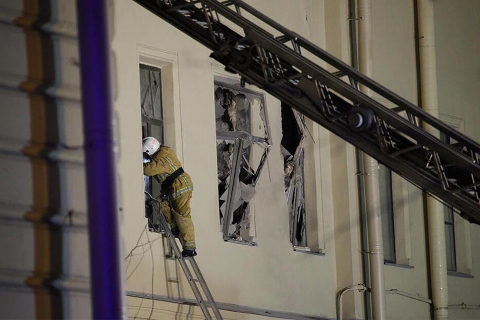 Ein Feuerwehrmann steigt durch ein Fenster eines Universitätsgebäude.