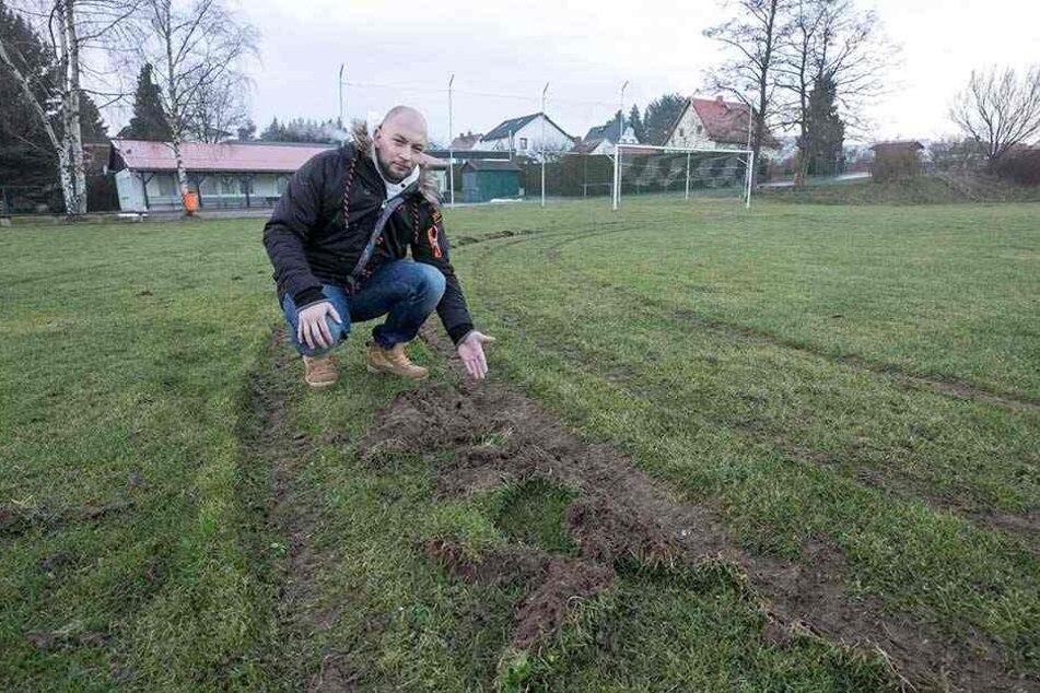 Fußball-Chef Martin Urban (31) zeigt den verwüsteten Rasen auf dem Spielplatz.