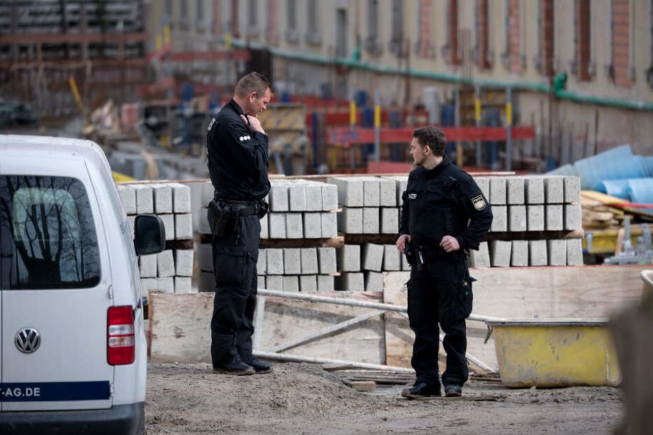 Zwei Polizisten stehen auf einer Baustelle: Hier wurden zwei tote Männer gefunden.