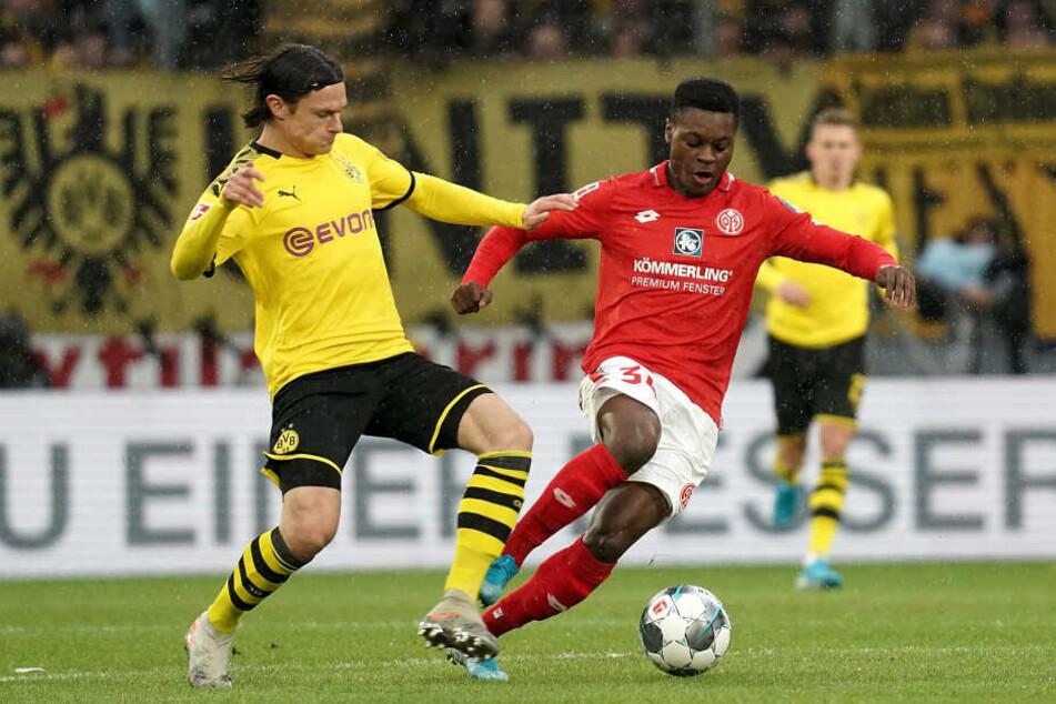 Der Mainzer Ridle Baku (r) neben Nico Schulz (l) aus Dortmund am Ball.