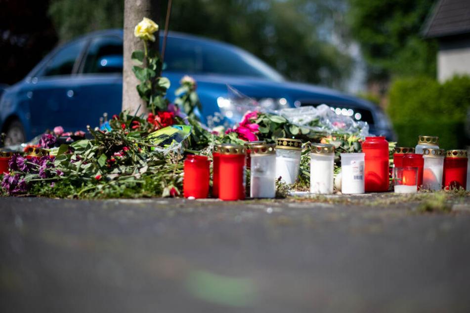 Blumen und Kerzen stehen in Moers an der Stelle, an der eine unbeteiligte Frau bei einem mutmaßlichen Autorennen verletzt und später gestorben ist.
