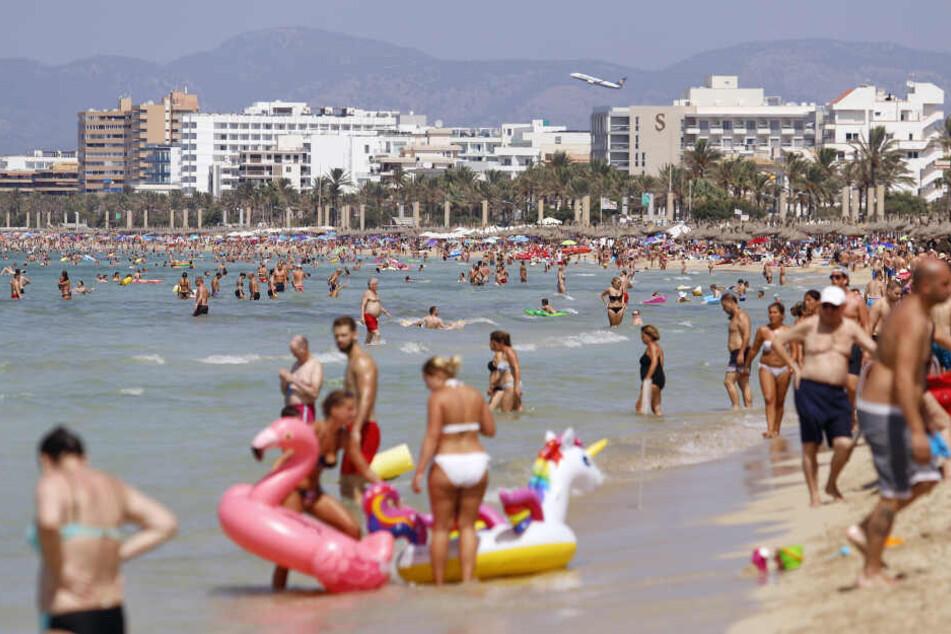 Touristen sonnen sich am Strand von El Arenal.