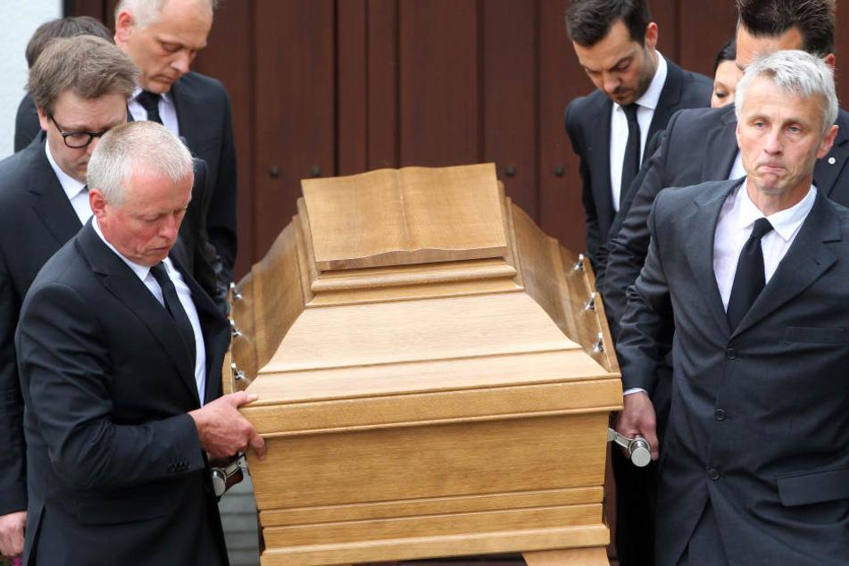 Acht Bestatter tragen den Sarg aus Helmut Kohls Haus.