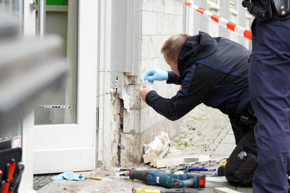 Ein Kriminalbeamter sichert das abgefeuerte Projektil an einem Türrahmen.