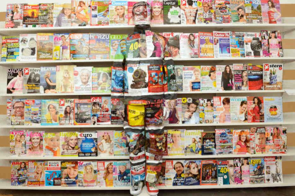 Der Künstler ist zwischen all den bunten Magazinen kaum auszumachen.